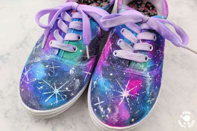 Pair of sneakers with galaxy space design painted on.