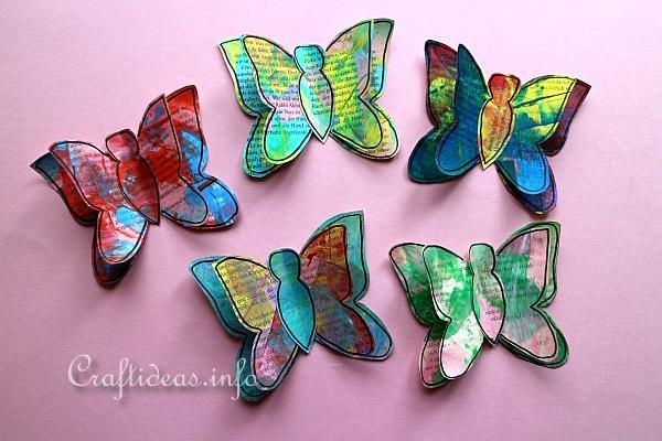 5 painted paper butterflies on a pink background.