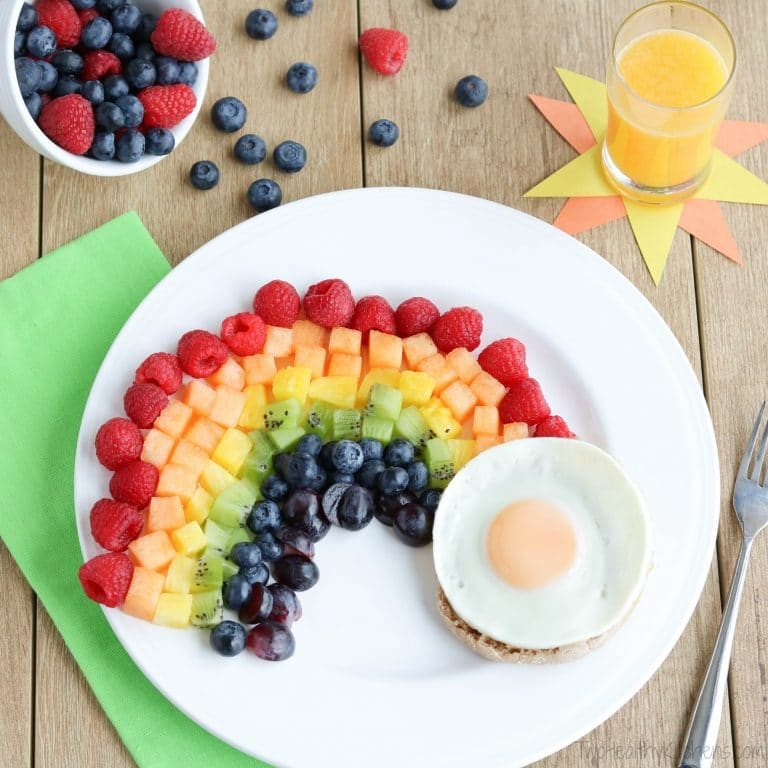 A rainbow made from fruit pieces on a white plate with a poached egg representing the pot of gold.