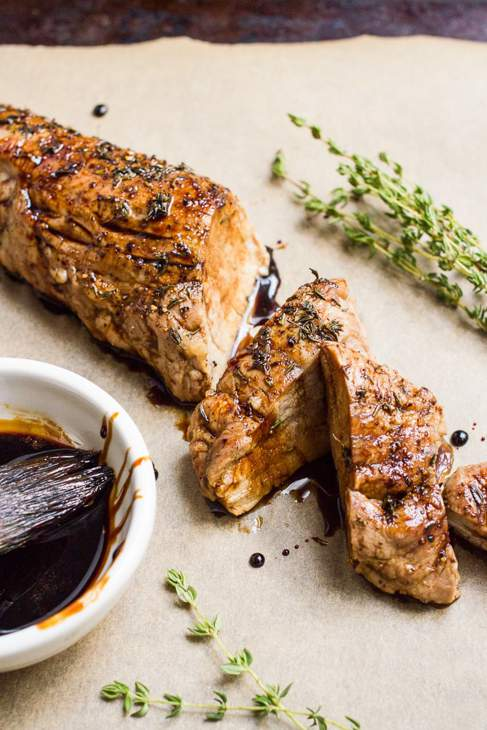 Cooked pork tenderloin including two slices, next to a white bowl of sauce and sprigs of thyme.