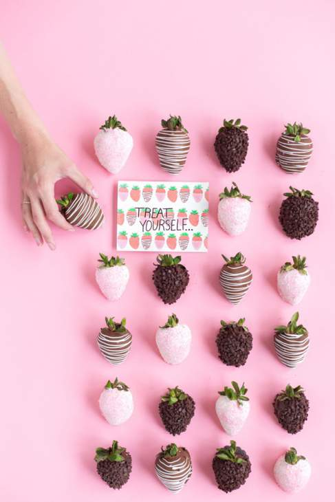 Arrangement of pink and chocolate coated strawberry sweets on a pink background. There is a card that says Treat Yourself, and a hand is removing one of the sweets.