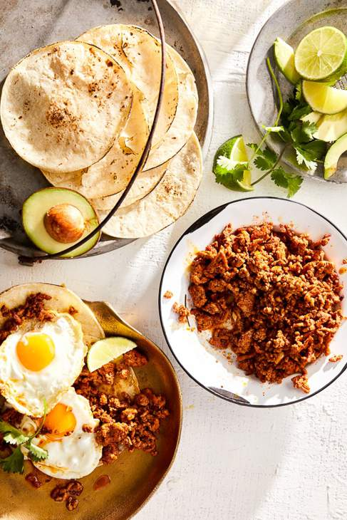 Table with various plates with eggs, avocado, limes, tortillas and meat.