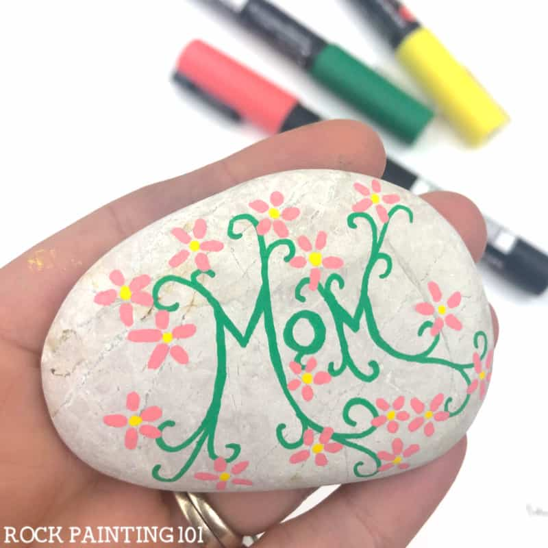 Hand holding a white stone with Mom written on it in ornate green script surrounded by pink flowers with yellow centres. In the background are colored pens in green, pink and yellow.