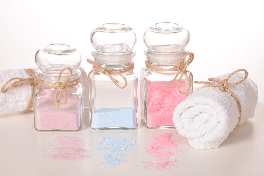 Three jars containing pink and pale blue colored bath salts, each with a string bow. Either side are two white towels tied with string bows.