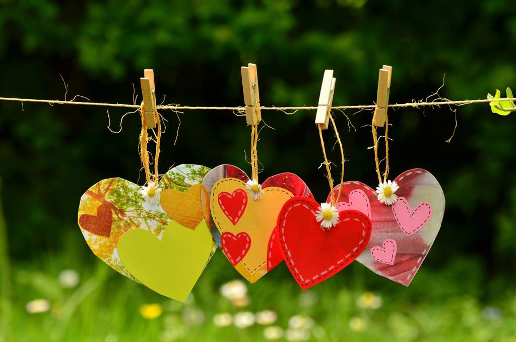Card and fabric hearts hanging from clothespins and string on a washing line. Each heart has a daisy in the middle.