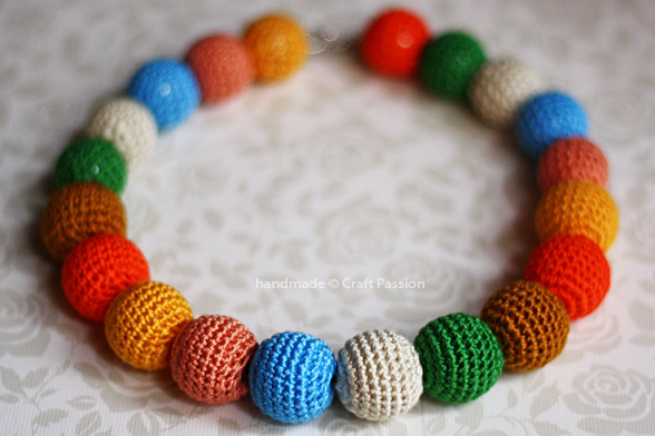 Necklace made from round crocheted beads of many different colors.