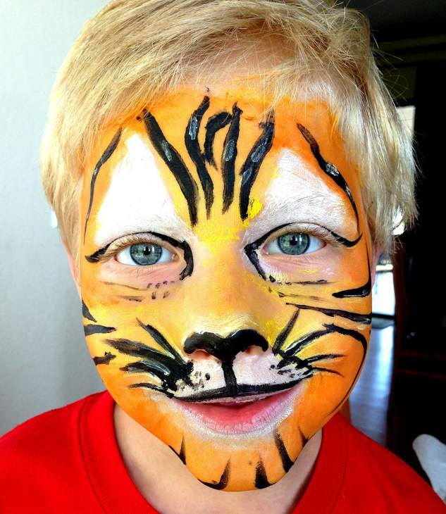 Young boy in red t-shirt wearing orange and white tiger face paint including a black nose, stripes and whiskers.
