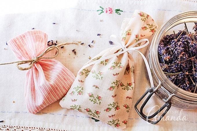 Two fabric pouches tied with ribbon and string next to a mason jar of lavender.