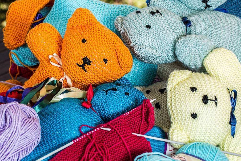 A heap of knitted teddy bears in lots of different colors.