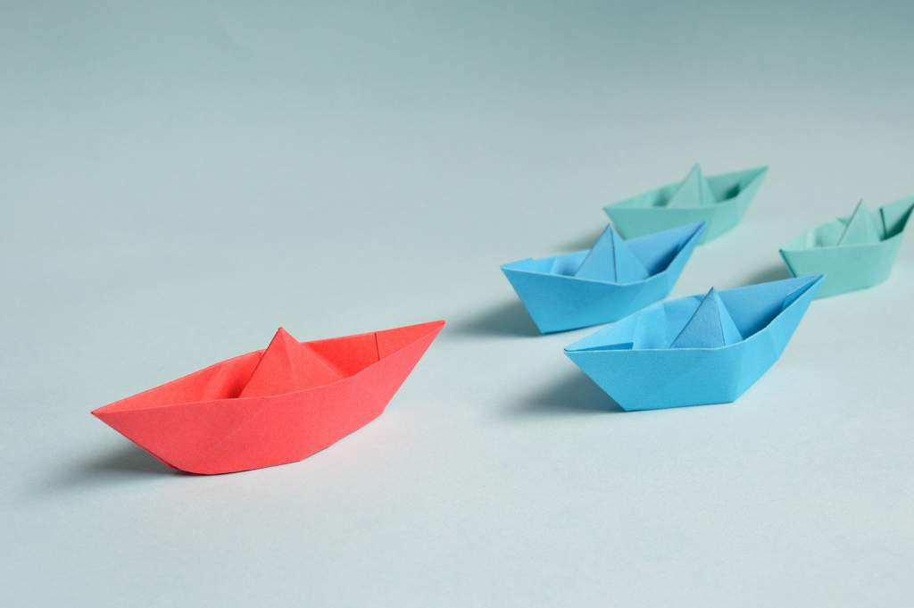 A red paper boat followed by four smaller blue and green paper boats.