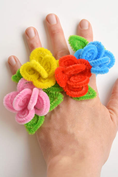A hand wearing 4 colorful flower shaped rings made from colored pipecleaners.