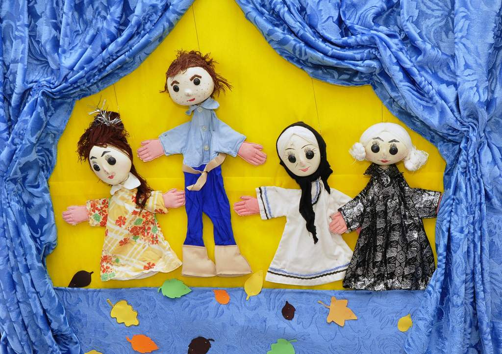 1 male and three female puppets on strings on a blue fabric stage with a yellow background with blue theatre curtains at the sides.