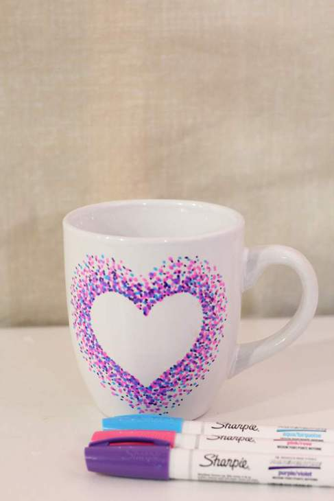 White mug decorated with a white heart outlined in purple pink and blue dots. Three Sharpie pens in those colors are lying in front of the mug..