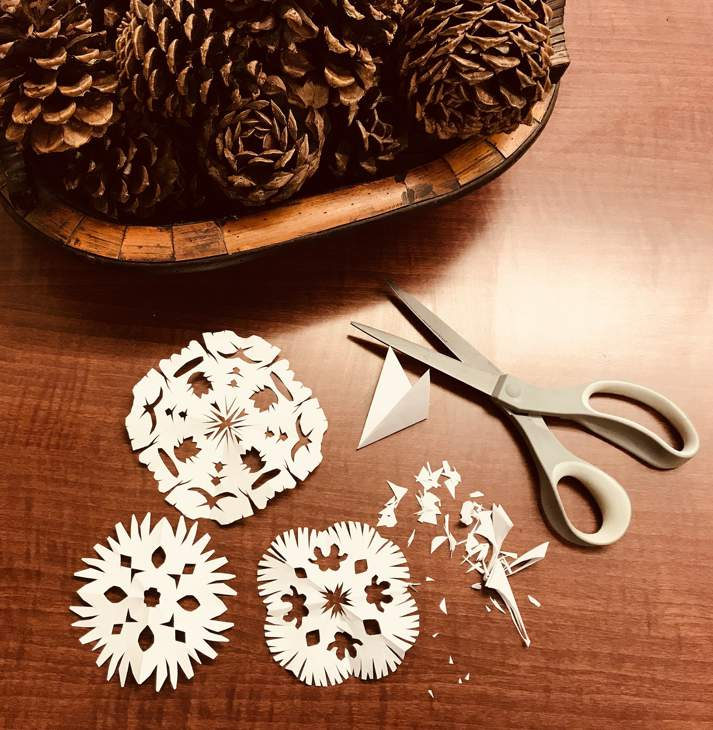 A basket of pinecones in the top left, and three paper snowflakes, a set of scissors and clippings from making the snowflakes, all on a wooden table.