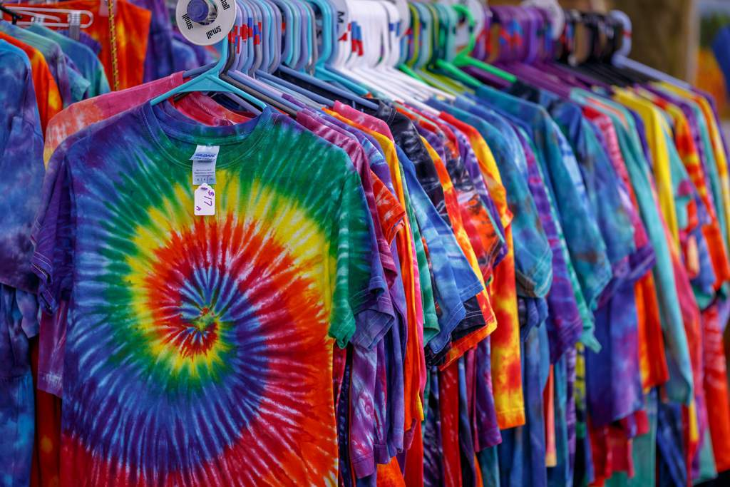 Lots of brightly colored tie-dye patterned t-shirts hanging on a rail.
