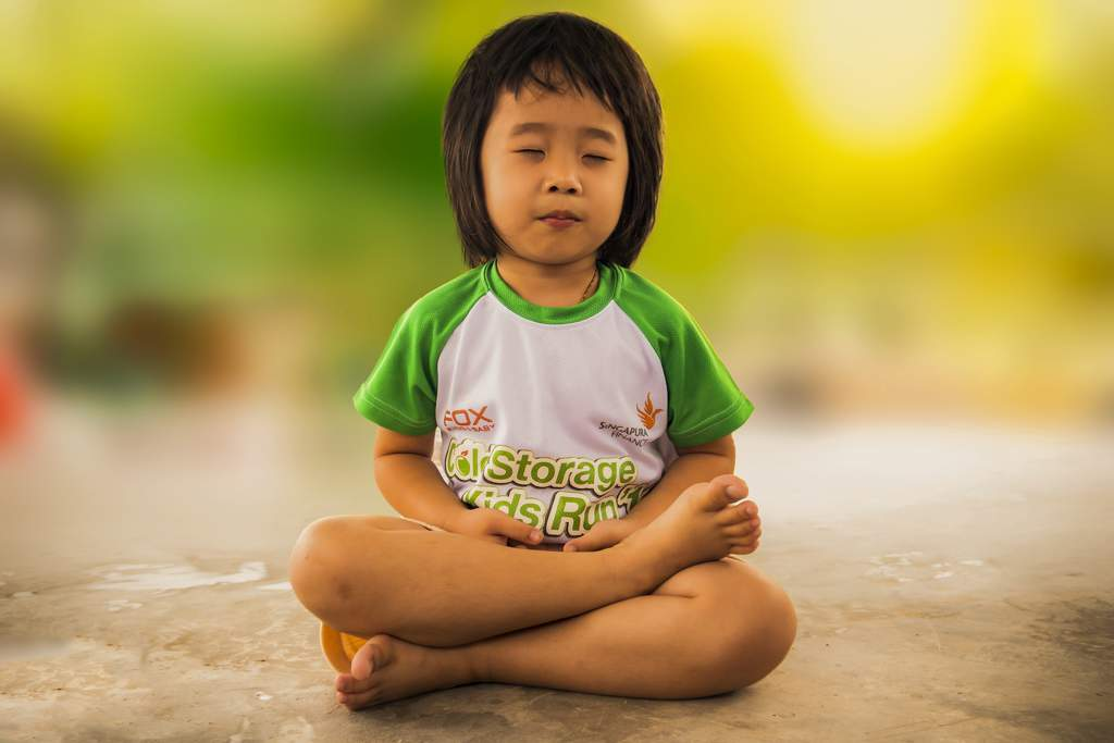 Child in a green t-shirt sitting cross-legged with her eyes closed.