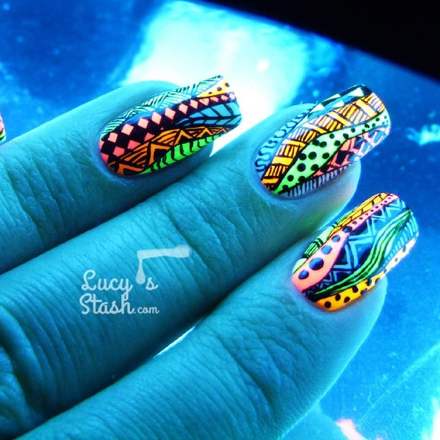 Hand looking blue under UV light, with neon-colored patterned nails glowing brightly in green orange and red colors.