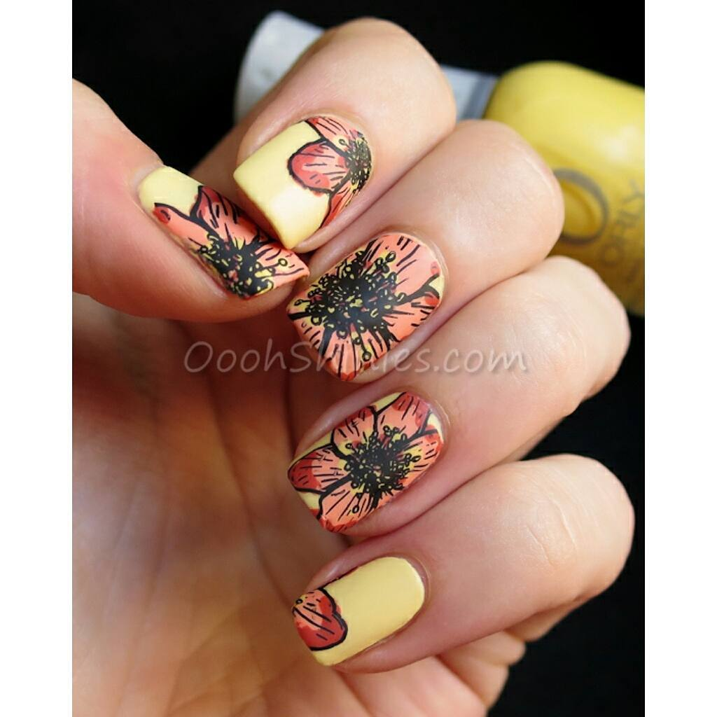 Hand with orange summer flower patterned nails on yellow backgrounds.