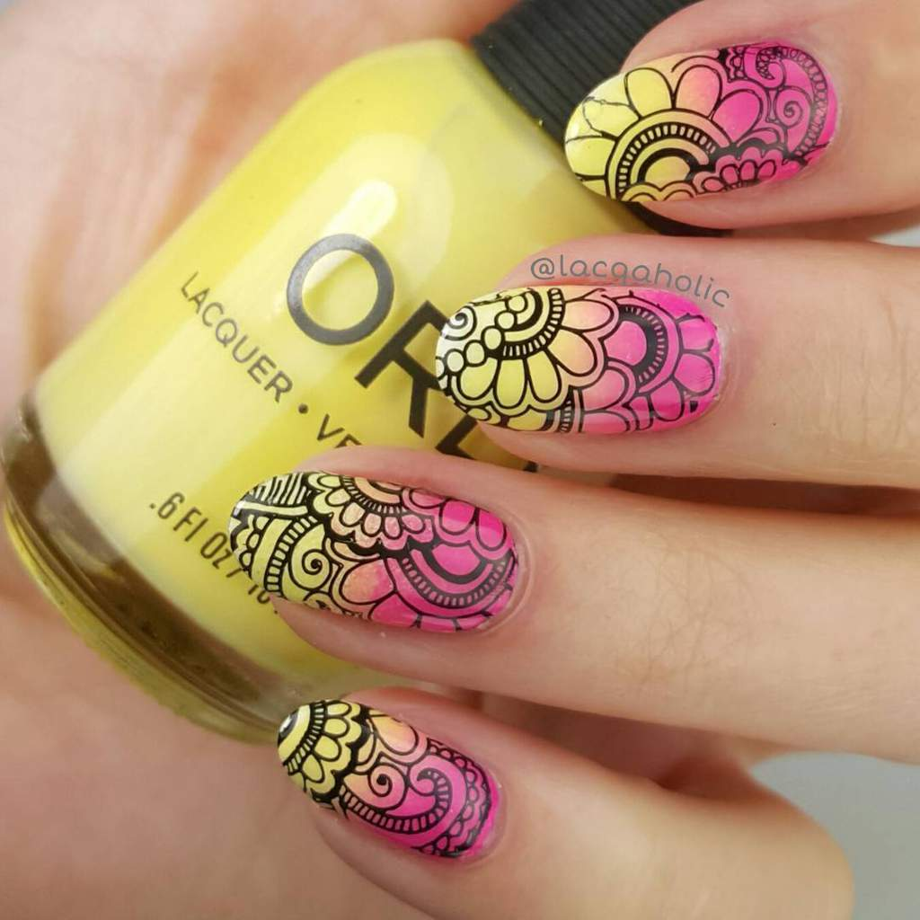 Hand holding a jar of yellow nail polish - fingernails are bright pink and yellow fades with black flower patterns.