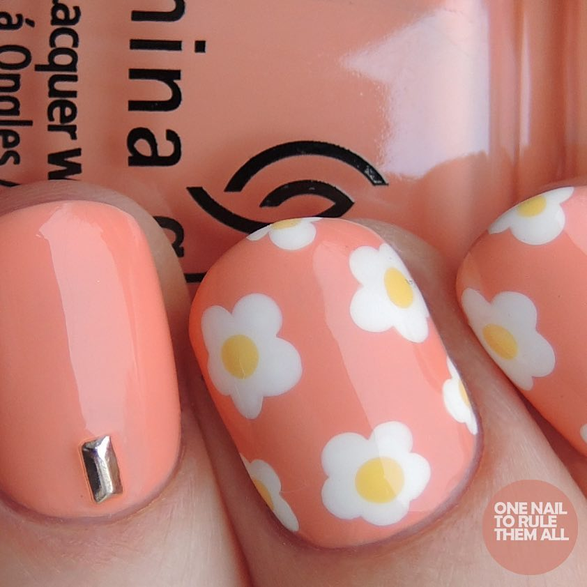 Pink nails with fried-egg flowers: White flowers with yellow centers