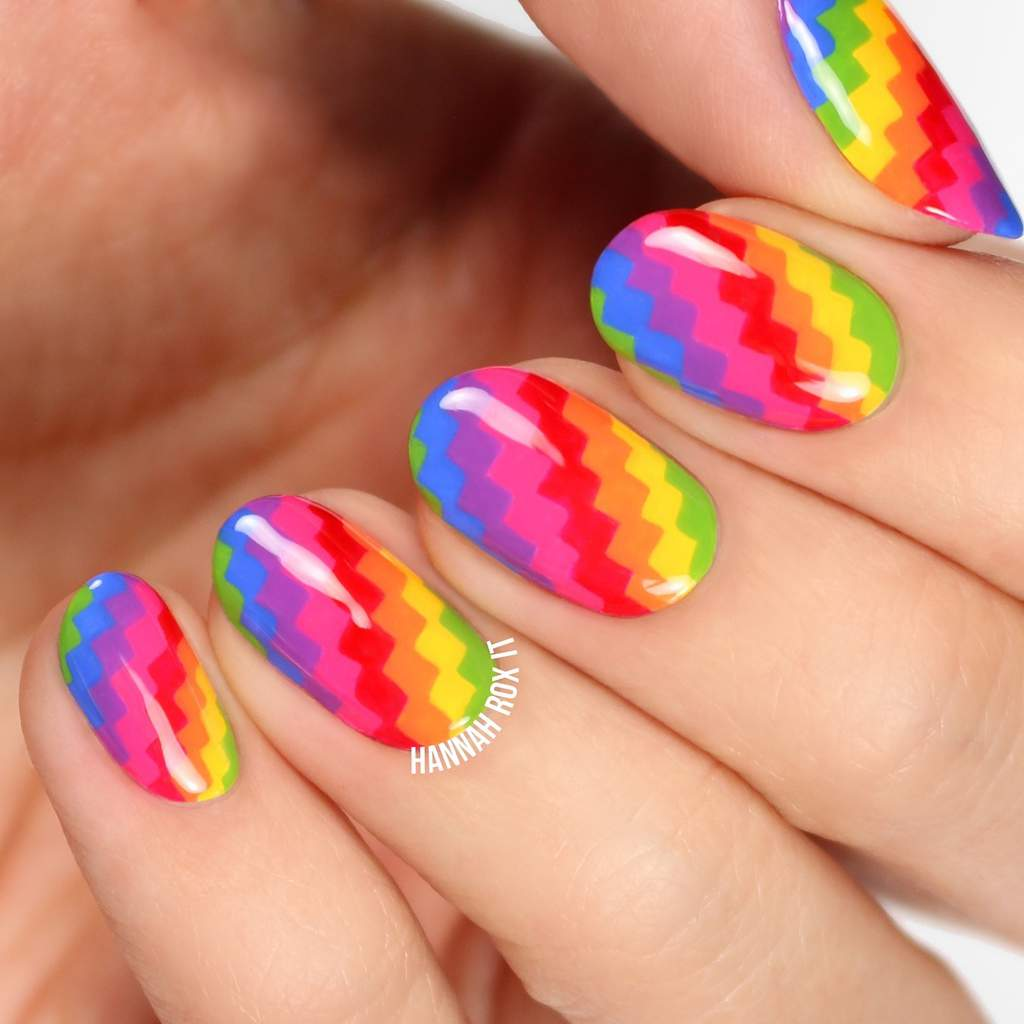 Fingernails with brightly colored pixellated rainbow pattern