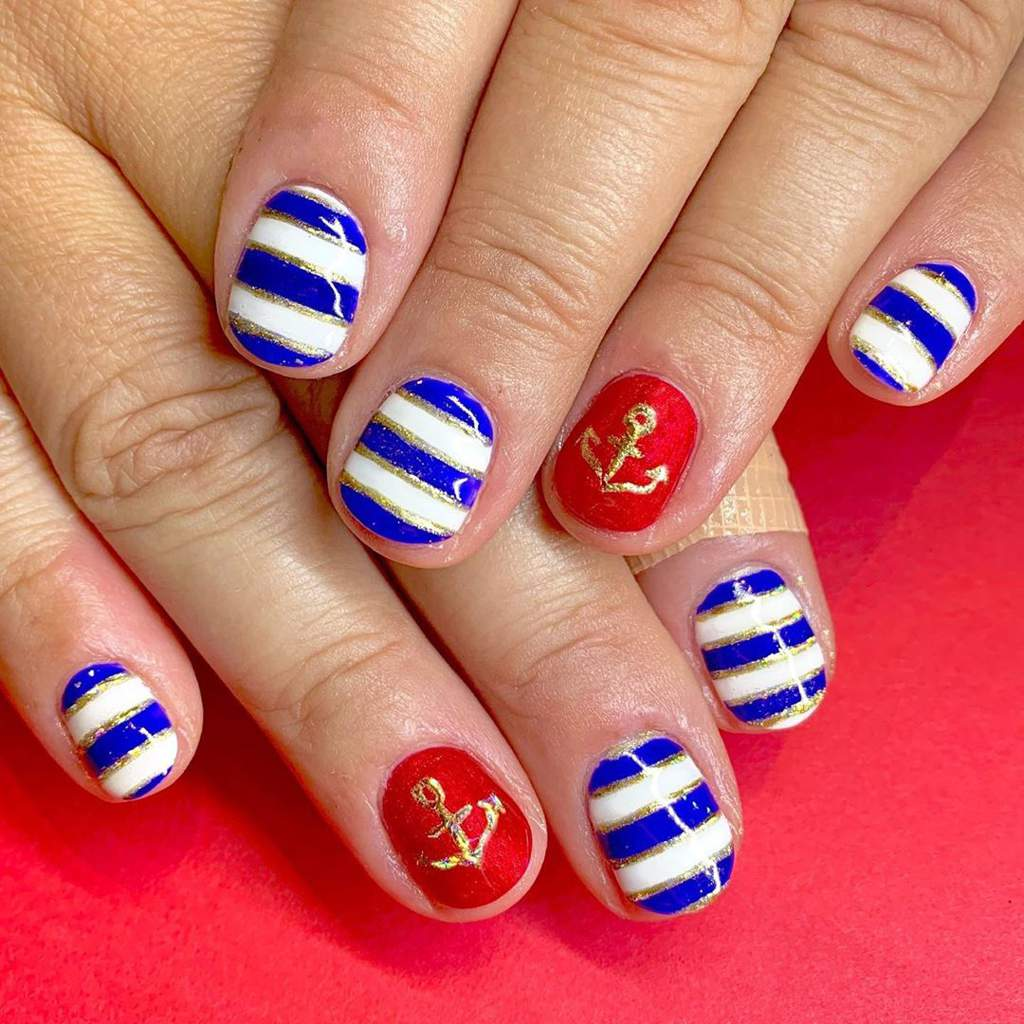 Nautical themed painted fingernails including blue, gold and white stripes, and gold anchors on a red background