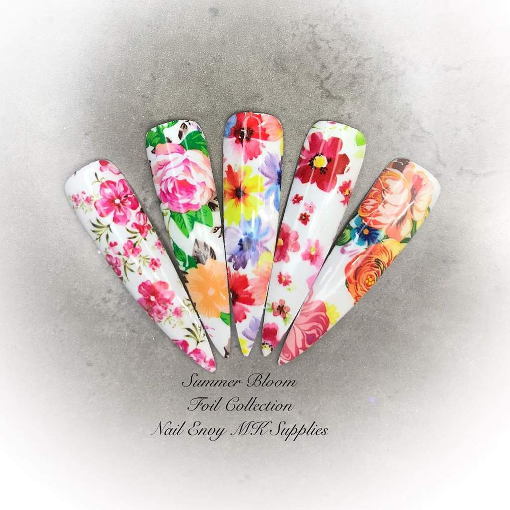 Five long artificial nails, each with a different summer flower pattern, on a white background..
