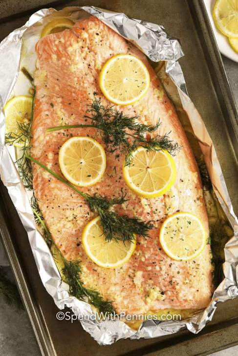 A baked salmon fresh from the oven, still in its foil, with lemon slices and herbs on top.
