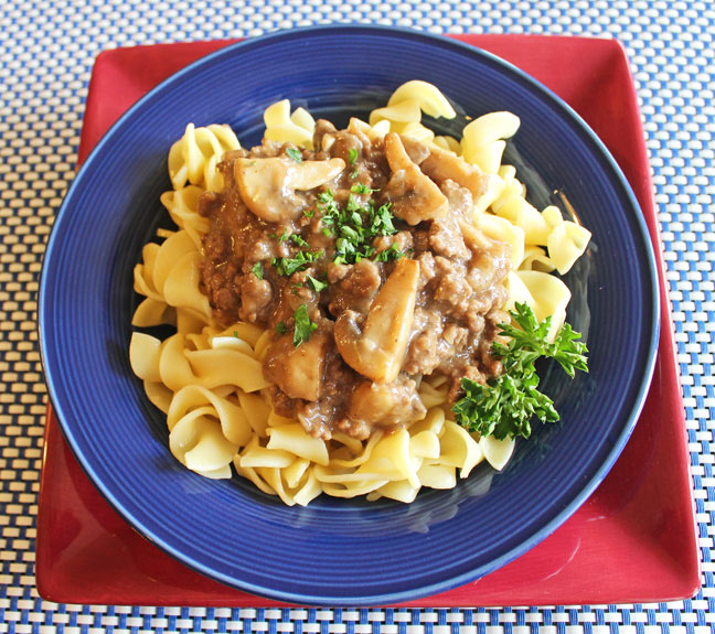 Beef stroganoff served on a bed of pasta in a blue bowl.