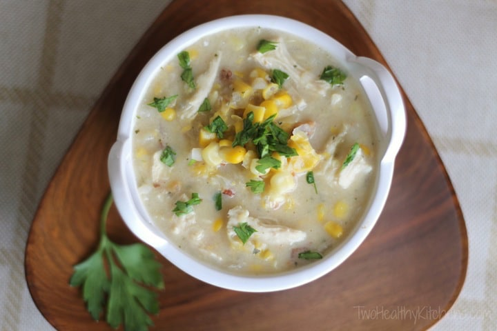 Chicken corn chowder served in a round white bowl on a triangular wooden placemat.