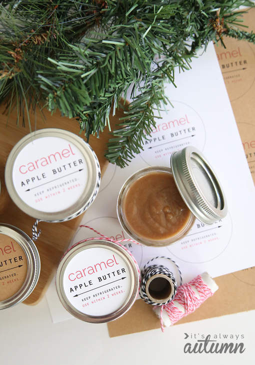 Four jars sitting on a sheet of labels under green foliage. The jar lids are labelled Caramel Apple Butter, and one jar has its lid removed to show the caramel-colored apple butter inside.