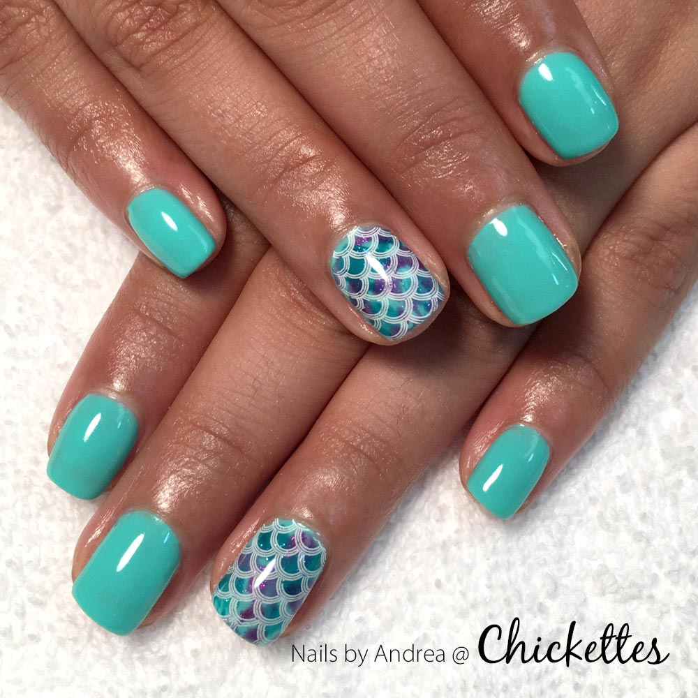 Painted fingernails with mermaid-themed designs - most nails are aqua color, but two have iridescent scales pattern.