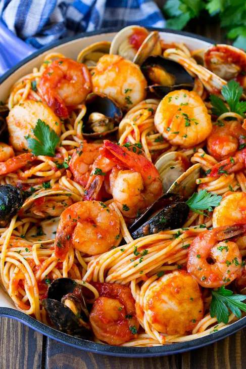 Seafood pasta with prawns and shellfish with pasta served in a blue and white bowl.